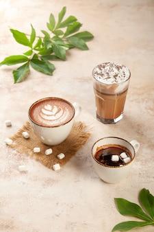 Café com leite, expresso, xícaras de cappuccino, marshmallow em fundo bege vintage