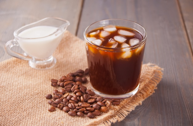 Café com leite gelado com cubos de gelo e grãos de café em uma mesa.