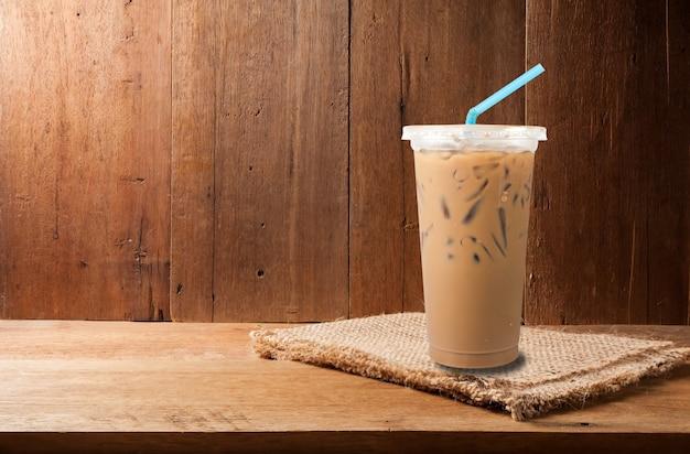 Café com leite gelado e grãos de café no espaço vazio da cópia de madeira