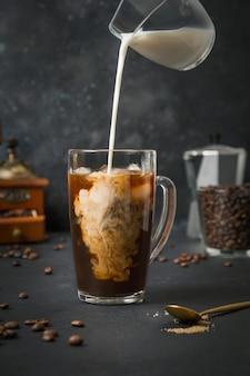 Café com leite gelado em copo de vidro com leite derramando em preto