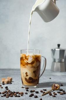 Café com leite gelado em copo de vidro com leite derramando