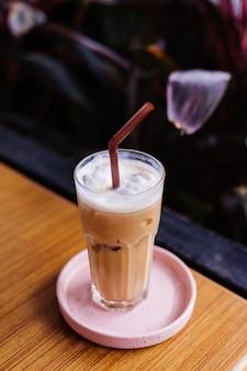 Café com leite gelado em vidro em um suporte rosa em uma mesa de madeira em arbustos verdes de café de verão