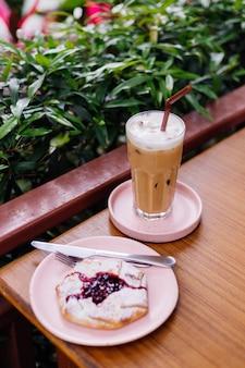 Café com leite gelado em vidro em um suporte rosa na mesa de madeira e torta de cranberry em arbustos verdes de café de verão