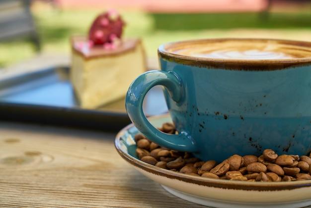 Café com leite, grãos de café e cheesecake na mesa de madeira