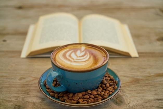 Café com leite, grãos de café e livro