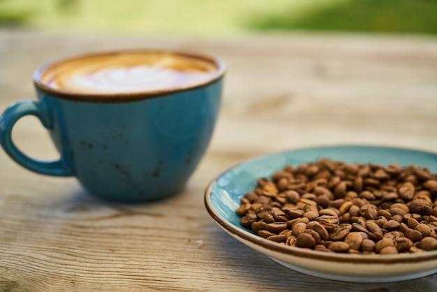 Café com leite, grãos de café na mesa