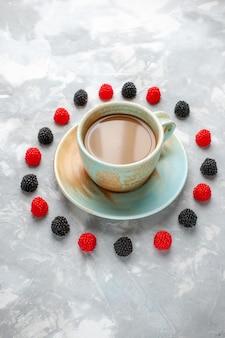 Café com leite junto com confitures de frutas vermelhas na mesa cinza-esbranquiçada