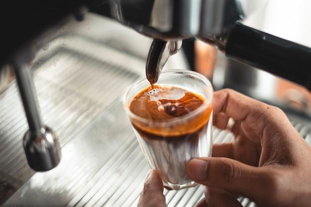Café com leite, leite e café em um copo da cafeteira