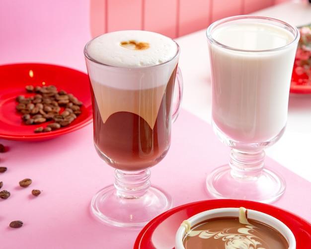 Café com leite macchiato com chocolate ao leite no vapor e grãos de café na mesa