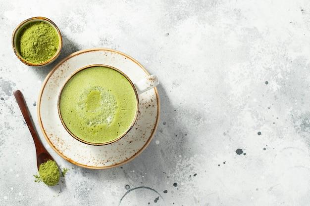 Café com leite matcha chá verde em uma xícara com creme.