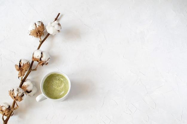 Café com leite matcha em copo branco ao lado do ramo de algodão seco