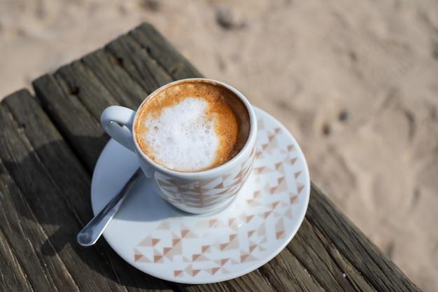 Café com leite na mesa de madeira na areia