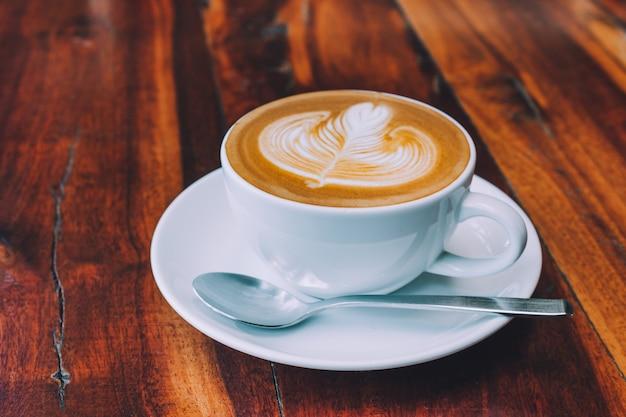 Café com leite na mesa de madeira na cafeteria