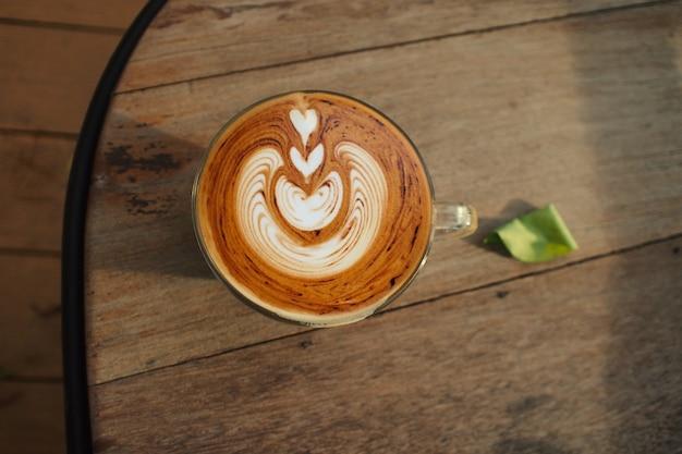 Café com leite na mesa de madeira, vista aérea