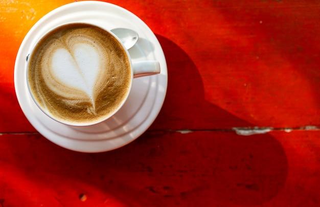 Café com leite na mesa, fundo vermelho, luz da manhã