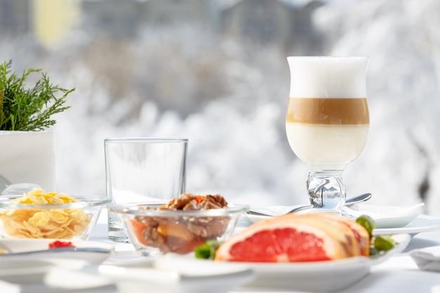Café com leite no terraço em frente ao restaurante contra a neve