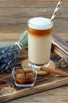 Café com leite ou cappuccino com espuma de leite e lavanda em copo alto na bandeja de madeira.