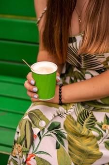 Café com leite para viagem em copo de papel verde nas mãos de uma jovem
