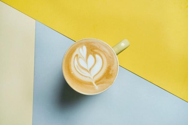Café com leite preparado na hora com camadas de leite, café e espuma em um copo amarelo sobre uma superfície colorida foto de café para o menu