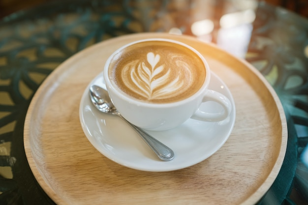 Café com leite quente arte na mesa de madeira, relaxe o tempo