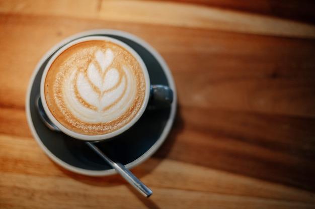 Café com leite quente colocado sobre uma mesa de madeira