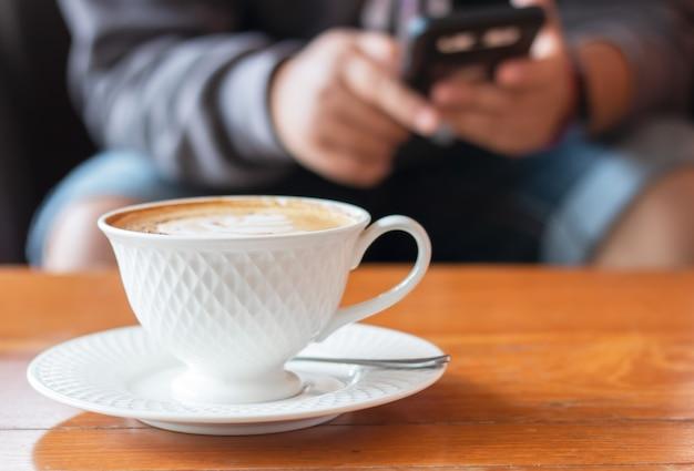 Café com leite quente em copo branco, homem que joga smartphone no café.