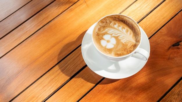 Café com leite quente em uma mesa de madeira.