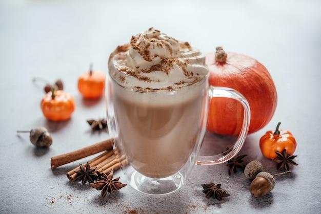Café com leite temperado outono com chantilly e canela em fundo de madeira, café com leite vegano outono com especiarias, canela e estrelas de anis