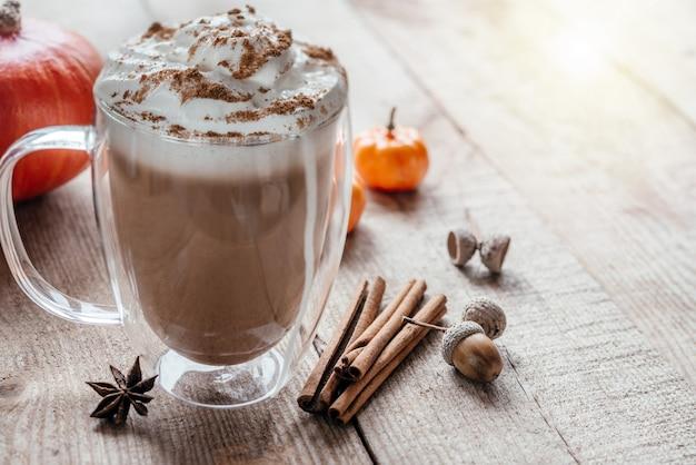 Café com leite temperado outono com chantilly e canela em fundo de madeira