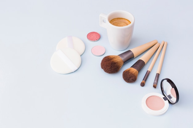 Café com pincel de maquiagem; sombra; esponja e blush em fundo branco