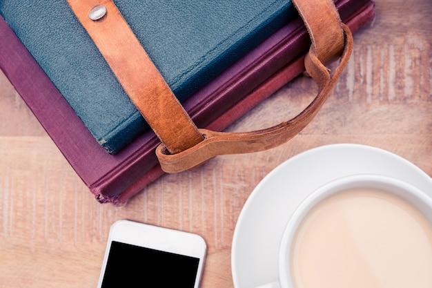 Café com smartphone e diários na mesa