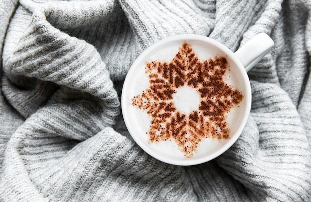 Café com um padrão de floco de neve em uma superfície quente de suéter de malha