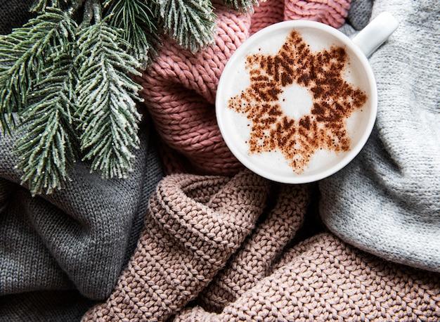 Café com um padrão de floco de neve em uma superfície quente de suéteres de malha