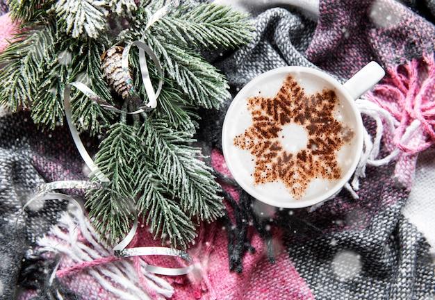 Ð¡café com um padrão de floco de neve em uma superfície xadrez de lã quente