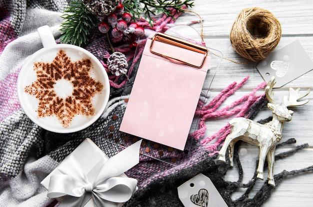 Café com um padrão de floco de neve sobre uma superfície quente de manta de lã, decorações de natal e um caderno de planos para o próximo ano