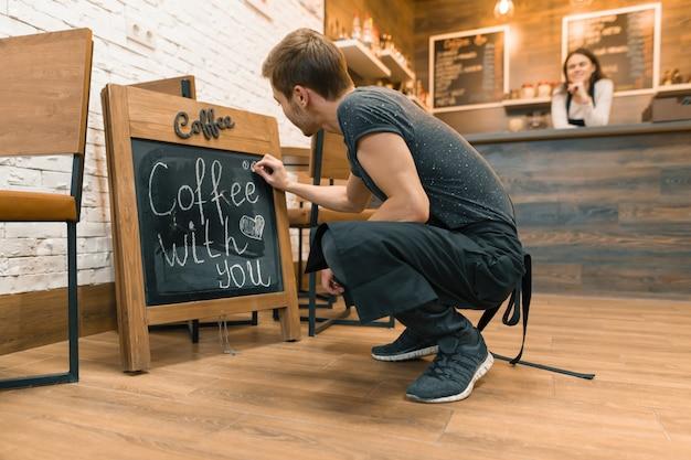 Café com você, escreve com giz no quadro-negro jovem trabalhador masculino