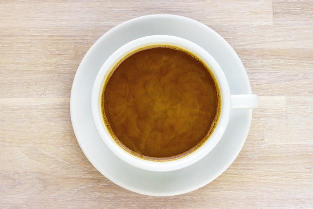 Café com xícara de leite, pires em madeira branca. conceito de pequeno-almoço de manhã. foco seletivo. copie o espaço. vista do topo. fechar-se