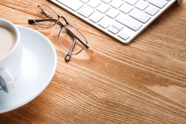 Café, computador e óculos em uma mesa de madeira