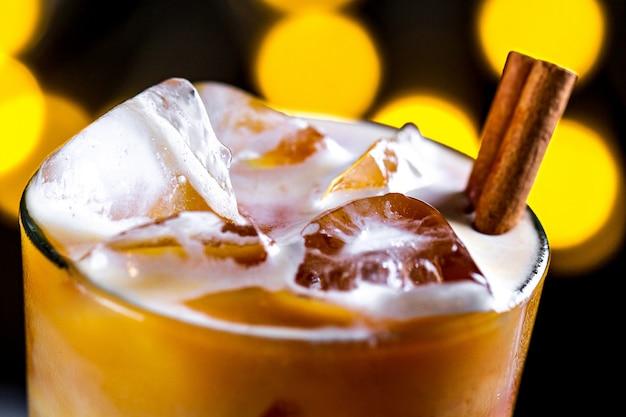 Café, coquetel refrescante com cubos de gelo, espuma e canela na superfície das luzes. bebidas frias