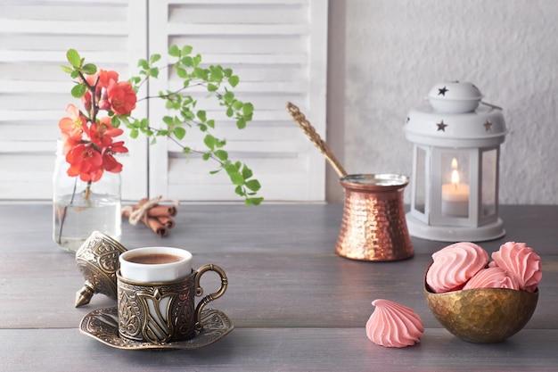 Café cozido no bule de café tradicional de cobre turco e servido em copo de metal cerâmico