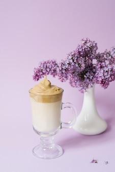 Café cremoso em copo de vidro com flores roxas em um vaso branco em fundo roxo claro