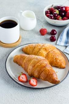 Café, croissants e frutas no café da manhã