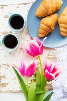 Café, croissants e três lindas tulipas cor de rosa na mesa branca velha