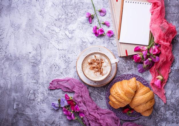 Café, croissants, flores e notebook.