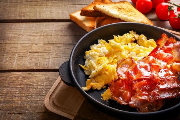 Café da manhã americano com ovos mexidos e bacon assado na madeira.