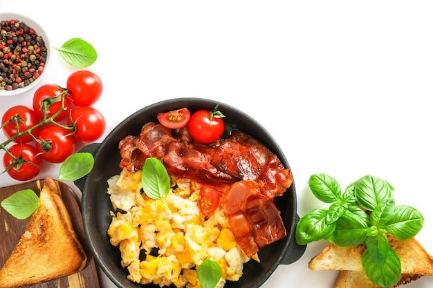 Café da manhã americano com ovos mexidos e bacon assado no branco.