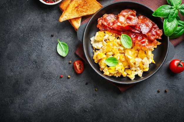 Café da manhã americano com ovos mexidos e bacon assado no escuro