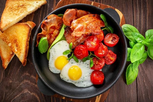 Café da manhã americano completo com ovos fritos e bacon assado em madeira
