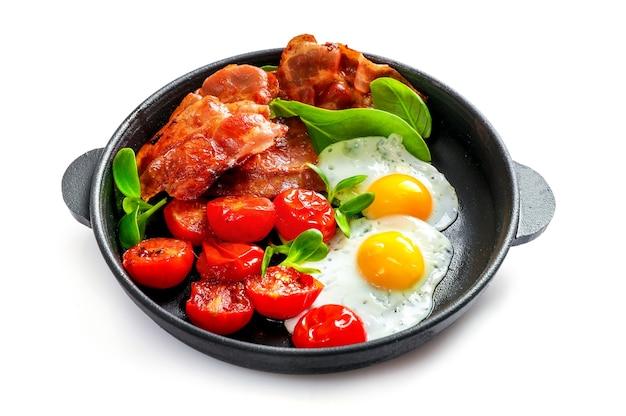 Café da manhã americano completo com ovos fritos e bacon assado isolado no branco.