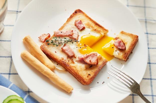 Café da manhã americano delicioso caseiro com ovo frito do estrelado, brinde, salsicha. café da manhã inglês com ovos fritos, bacon, salsichas e torradas. café da manhã no dia dos namorados. bom dia conceito